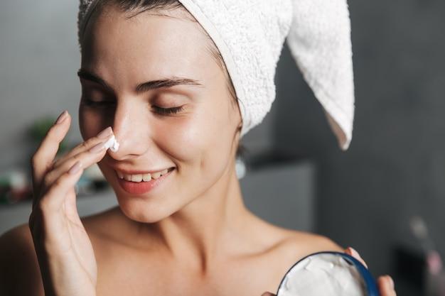 Close da foto de uma mulher satisfeita enrolada em uma toalha na cabeça, aplicando creme no rosto