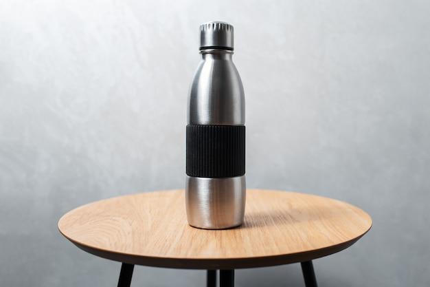 Close da garrafa de água térmica reutilizável de aço na mesa de madeira contra o fundo da parede cinza texturizada.