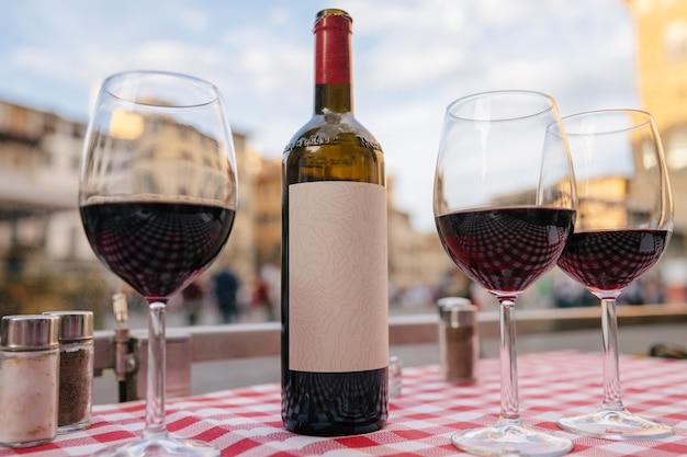 Close da garrafa de vinho tinto e copos na mesa do restaurante no fundo da piazza della signoria em dia de verão