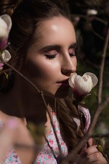 Close da glamourosa mulher morena em pé perto de flores de magnólia desabrochando
