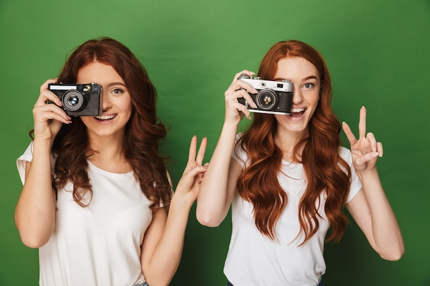 Close da imagem de duas mulheres ruivas de 20 anos fazendo fotos com você na câmera retro e gesticulando o sinal da vitória, isolado sobre um fundo verde