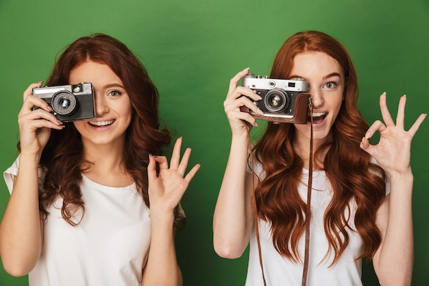 Close da imagem de duas mulheres ruivas de 20 anos fotografando você na câmera retro e gesticulando para o símbolo ok, isolado sobre um fundo verde