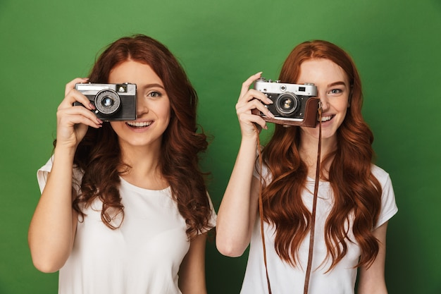 Close da imagem de duas mulheres ruivas de 20 anos segurando e fotografando você em uma câmera retro, isolada sobre um fundo verde
