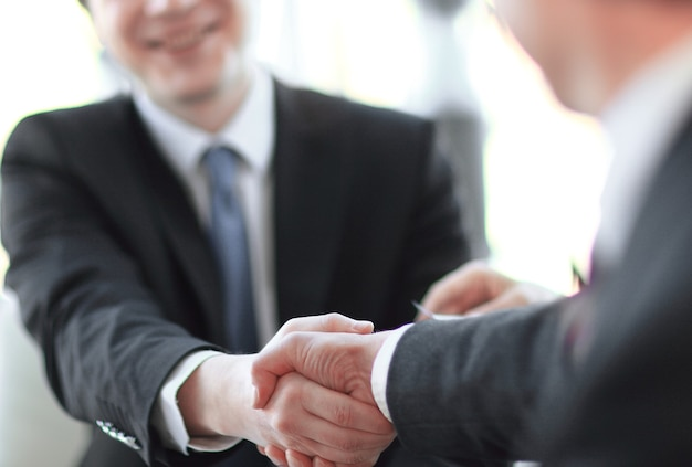 Close da imagem de fundo de um aperto de mão de parceiros de negócios. o conceito de parceria