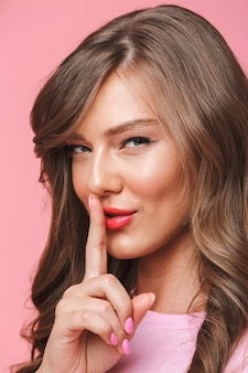 Close da imagem de uma jovem mulher bonita de 20 anos com um penteado encaracolado longo, sorrindo enquanto segura o dedo na boca com segredo, isolado sobre um fundo rosa