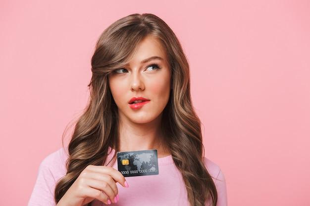 Close da imagem de uma mulher europeia em roupas casuais, mordendo os lábios e segurando o cartão de crédito enquanto fazia compras na internet, isolado sobre o fundo rosa