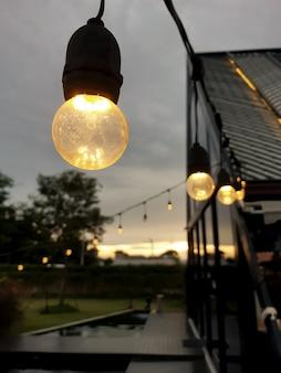 Close da lâmpada de luz amarela contra o pôr do sol na foto de alta qualidade
