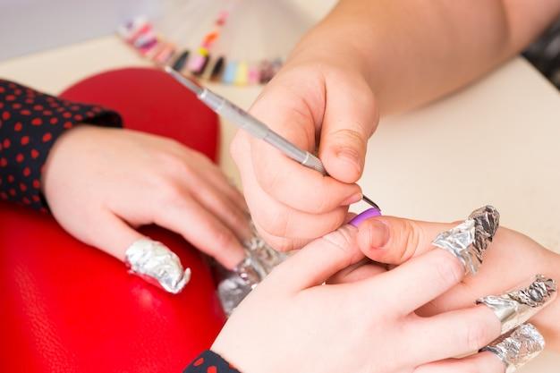 Close da manicure usando ferramenta de modelagem nas unhas dos dedos de uma cliente com as mãos envoltas em papel alumínio durante manicure com gel no spa