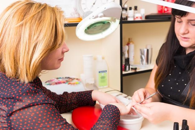 Close da manicure usando uma ferramenta para moldar e limar as unhas dos dedos de uma cliente loira, mergulhando as mãos em pequenas tigelas de água durante o tratamento de manicure no spa