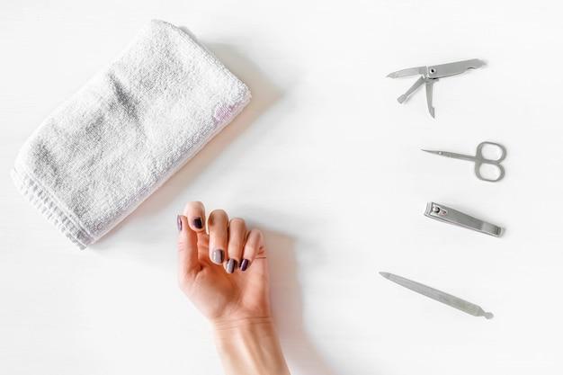 Close da mão da mulher com unhas polidas e instrumentos de manicure. mulher caucasiana, recebendo manicure francesa em casa ou no salão de beleza. manicure, autocuidado, procedimentos de beleza você mesmo.