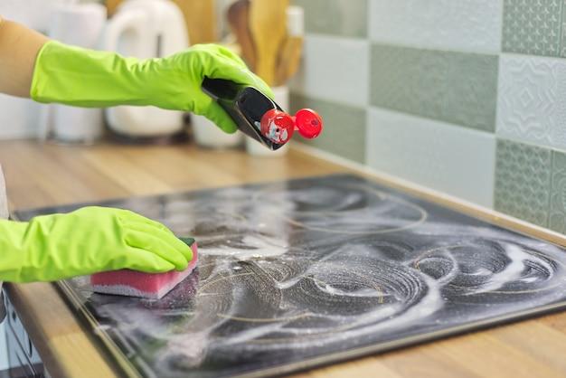 Close da mão da mulher limpando a superfície elétrica de cerâmica de vidro para cozinhar moderna com esponja e detergente