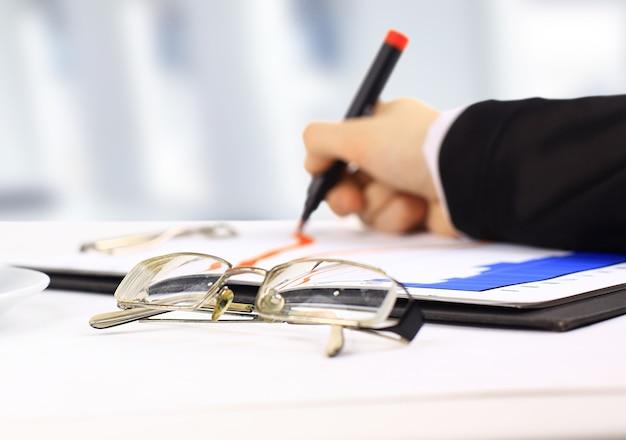 Close da mão da senhora de negócios com uma caneta, assinando um contrato