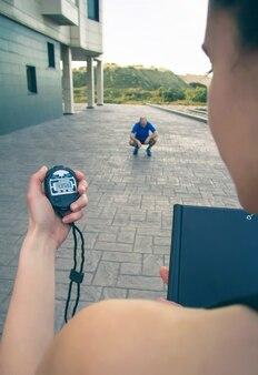Close da mão da treinadora usando um cronômetro para cronometrar o homem atlético cansado em um treinamento intenso ao ar livre