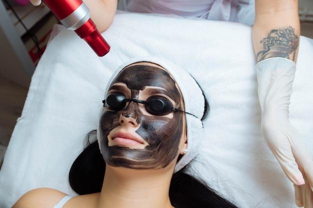 Close da mão de cosmetologistas fazendo casca de carbono de hardware por uma jovem e bela cliente em cofre ...