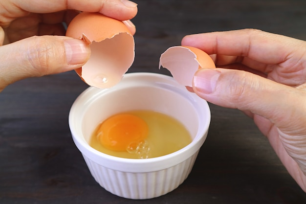 Close da mão de um homem quebrando um ovo em uma tigela