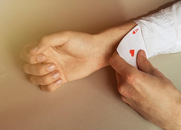 Close da mão de um homem removendo o ás das mangas