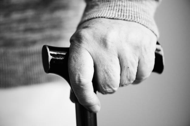 Close da mão de um idoso segurando uma bengala