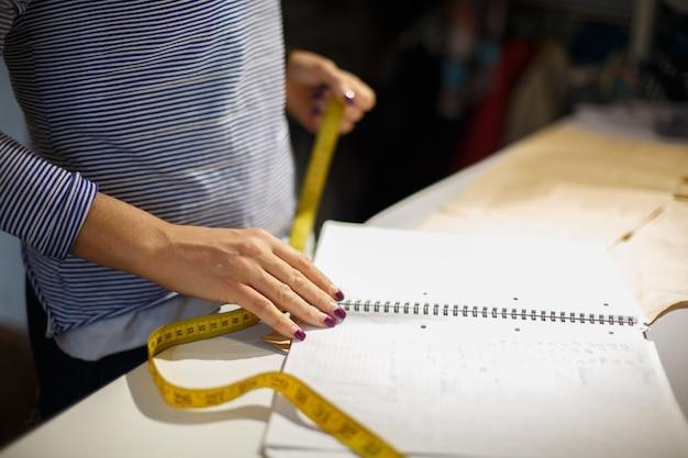 Close da mão de uma costureira com um centímetro. mede a linha de corte do tecido por espaços em branco