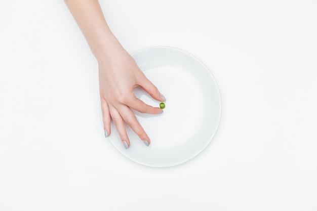 Close da mão de uma jovem tirando uma pequena ervilha verde do prato