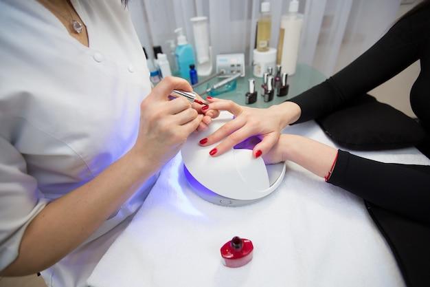 Close da mão de uma manicure que aplica esmalte gel vermelho nas unhas de uma jovem. menina seca o esmalte de gel na lâmpada uv.