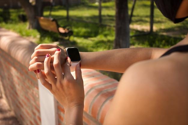Close da mão de uma menina configurando um relógio inteligente para exercícios