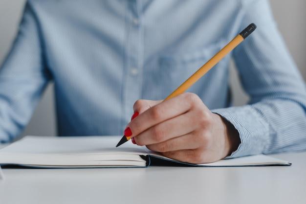 Close da mão de uma mulher com unhas vermelhas, escrevendo em um caderno com um lápis amarelo.