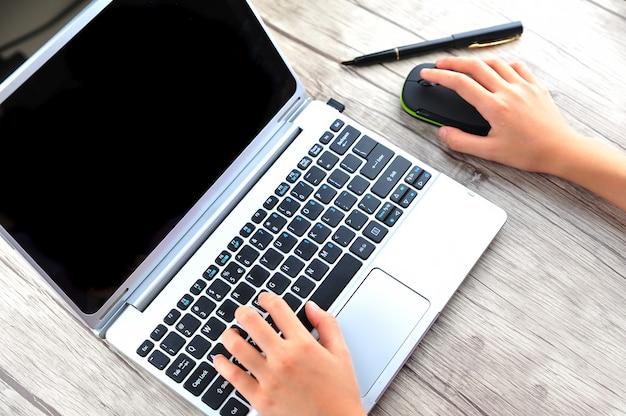 Close da mão de uma mulher de negócios digitando no teclado do laptop com o mouse