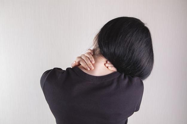 Close da mão de uma mulher massageando seu pescoço. pescoço da menina dói