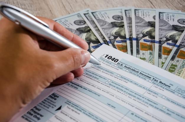Close da mão de uma mulher preenche formulários de impostos 1040