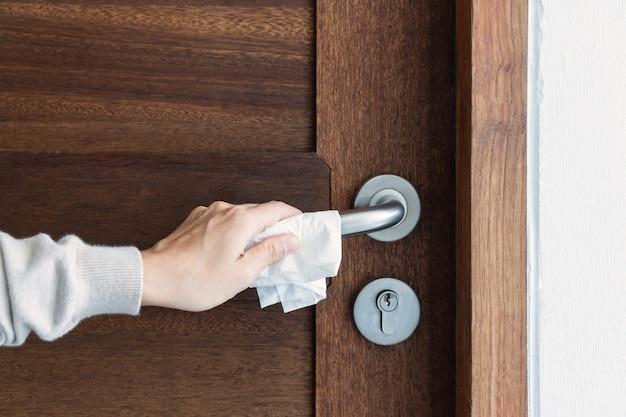 Close da mão de uma mulher segurando a maçaneta da porta através de um lenço de papel
