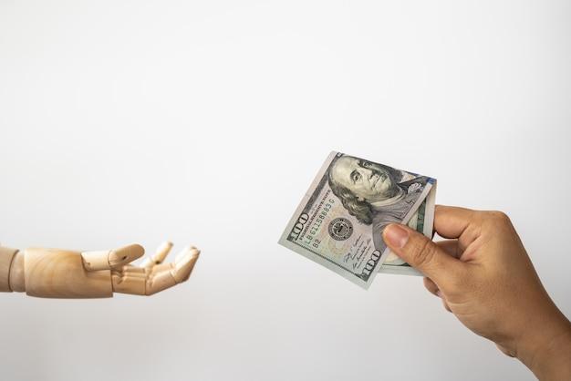 Close da mão de uma mulher segurando e dar uma nota de banco de 100 dólares americanos ao modelo de mão de madeira.