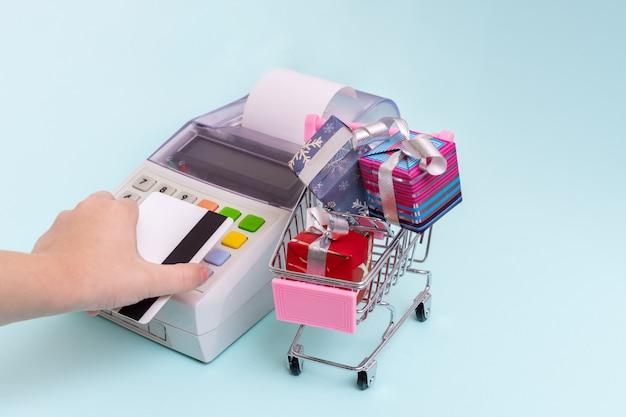 Close da mão de uma mulher segurando um cartão do banco sobre um terminal de caixa registradora para pagar compras em um carrinho com caixas de presente, vista frontal