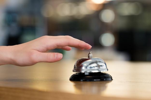 Close da mão de uma mulher tocando a campainha no hotel na recepção