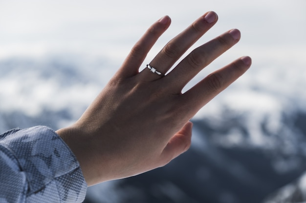 Close da mão de uma mulher usando um anel em frente à montanha