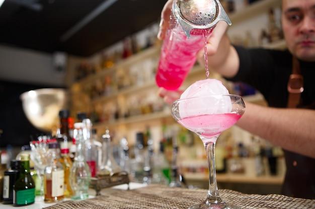 Close da mão do barman servindo coquetel rosa em bar
