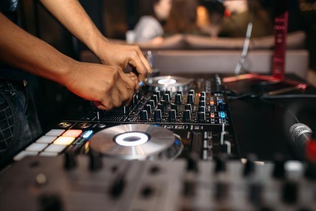 Close da mão do dj tocando música em uma plataforma giratória em um festival de festa
