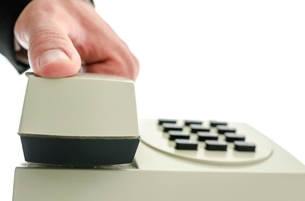 Close da mão do empresário segurando o receptor do telefone como se ele estivesse atendendo ou desligando o telefone. isolado sobre fundo branco.