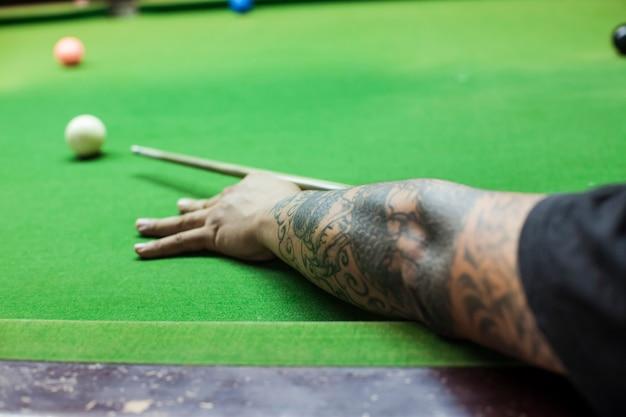 Close da mão do homem com taco de bilhar pronto para acertar a bola branca