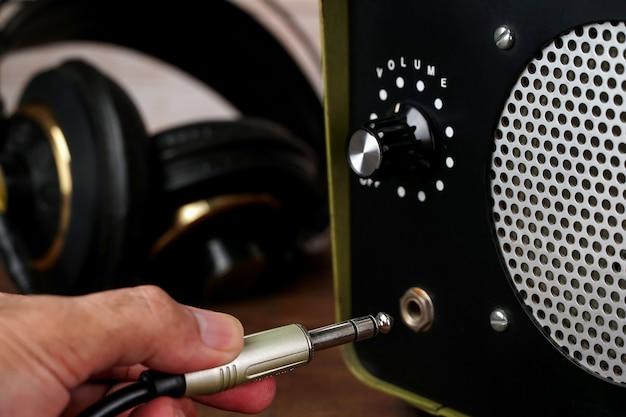 Close da mão do homem conectando o cabo do fone de ouvido ao conector do amplificador trs