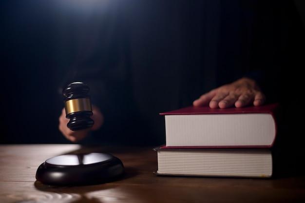 Close da mão do juiz batendo no martelo do juiz no tribunal