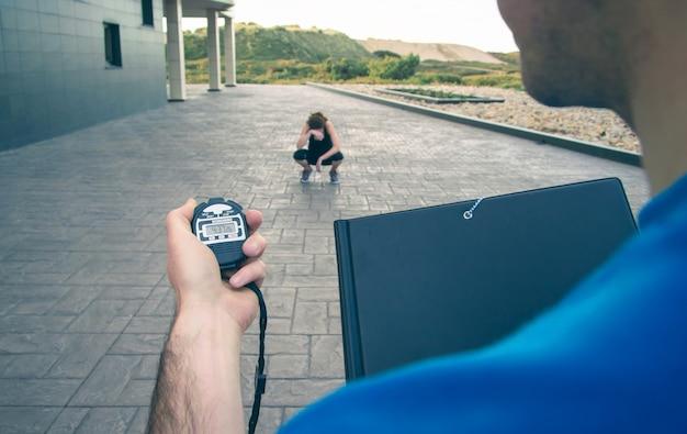 Close da mão do treinador masculino usando um cronômetro para cronometrar uma jovem atlética cansada em um treinamento intenso ao ar livre