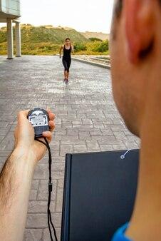 Close da mão do treinador masculino usando um cronômetro para cronometrar uma jovem atlética em um treinamento intenso ao ar livre