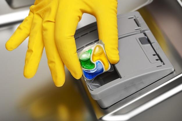 Close da mão em uma luva de borracha amarela, colocando o tablete de detergente na água da louça