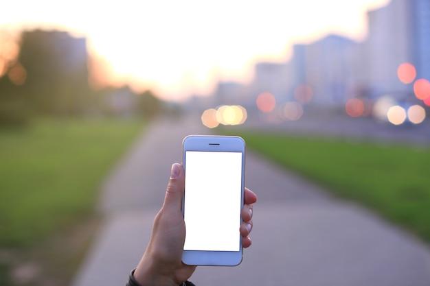 Close da mão feminina segurando um smartphone moderno com tela em branco, exibição na cidade à noite.