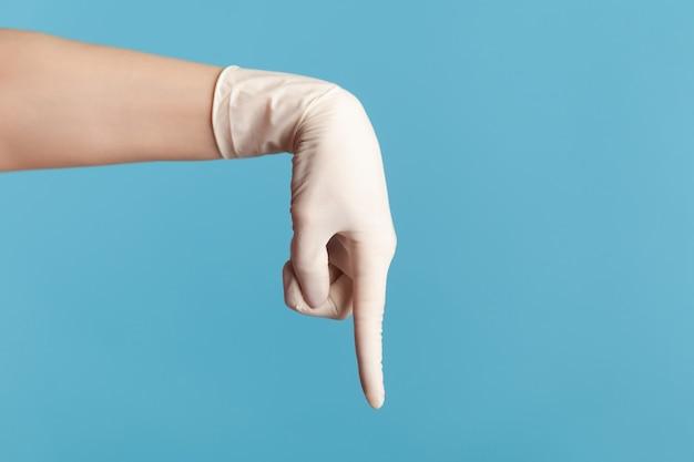 Close da mão humana em luvas cirúrgicas brancas, mostrando ou apontando para baixo com o dedo.
