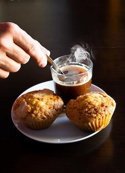 Close da mão misturando café com uma colher ao lado de muffins frescos