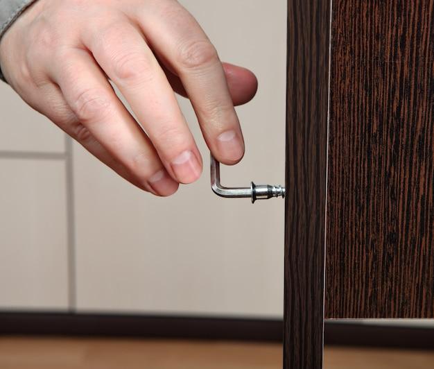Close da mão parafusada chave allen, montagem de móveis.