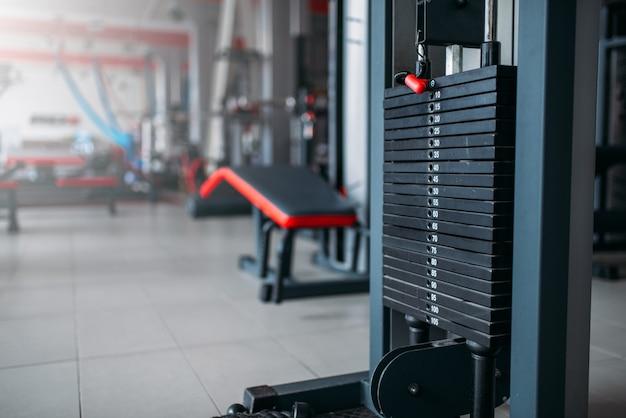 Close da máquina de exercícios, equipamento de esporte na academia, interior do clube de fitness