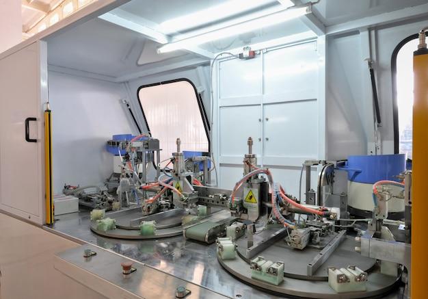 Close da máquina para fabricação e montagem de dobradiças de portas e janelas