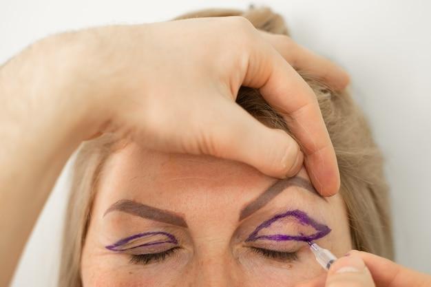 Close da marcação de blefaroplastia no rosto antes da operação de cirurgia plástica para modificação da região ocular da face em clínica médica. médico fazendo operação plástica de cosmética